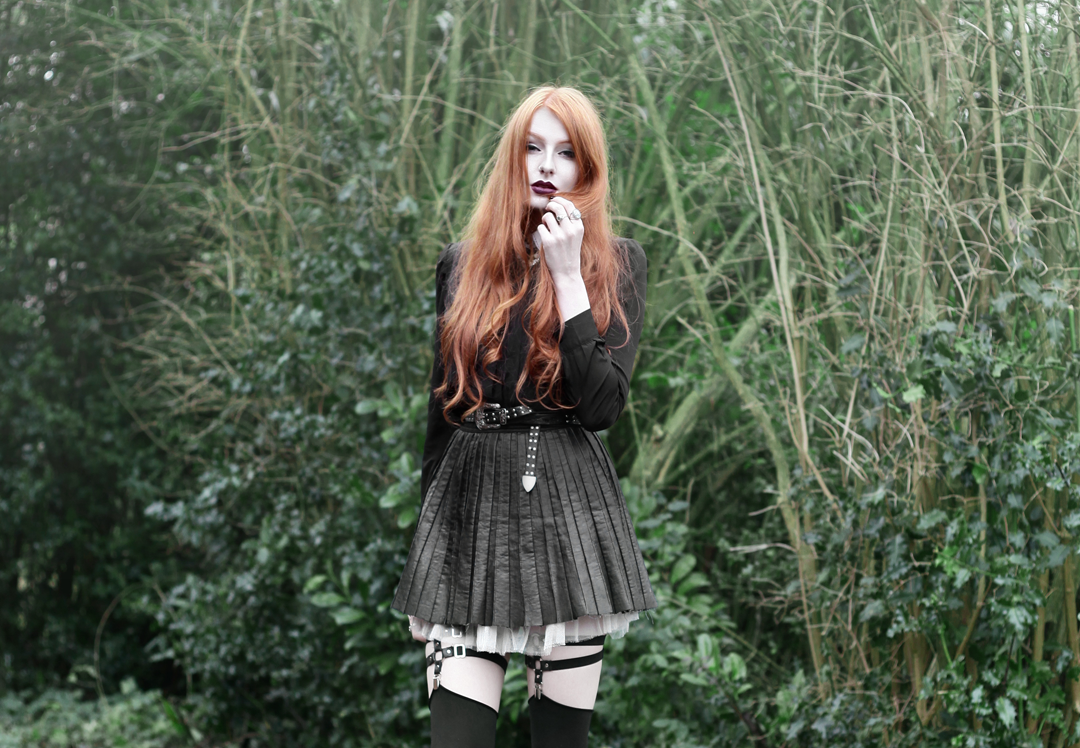 Olivia Emily wears Contrast Collar Black Blouse, Asos Western Belt, Pleated Faux Leather Skirt, Jakimac Leg Garter Harnesses, Unif Red Velvet Hellbound Boots