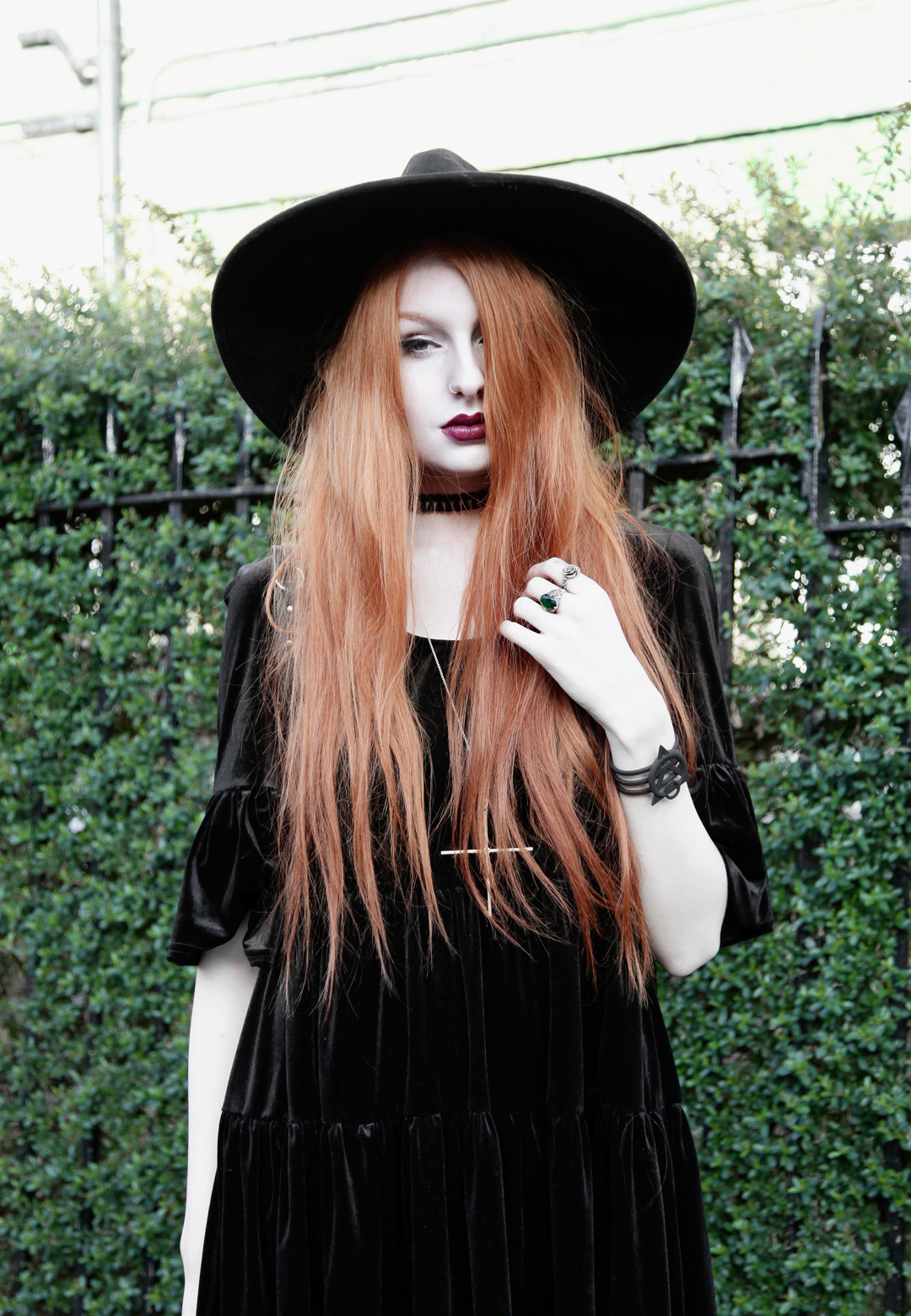 Olivia Emily wears Asos Reclaimed Vintage tiered black velvet dress, Killstar Witch Brim hat, and Kiki Minchin Classic Cross silver necklace