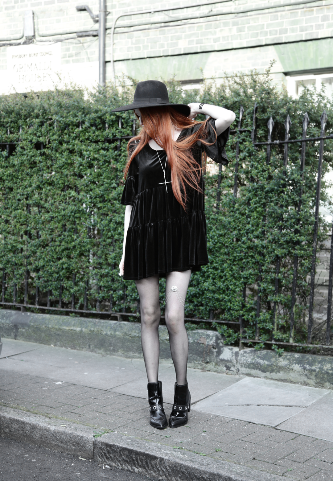 Olivia Emily wears Asos Reclaimed Vintage tiered black velvet dress, Killstar Witch Brim hat, River Island leg chain, and Asos eyelet boots