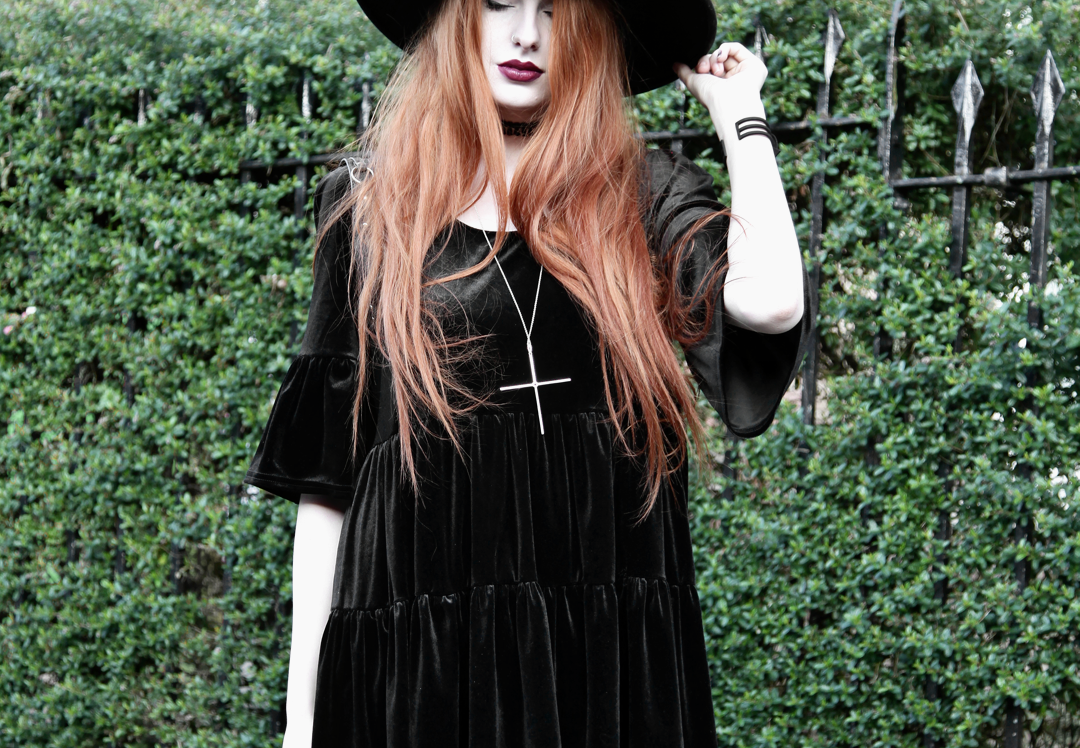 Olivia Emily wears Asos Reclaimed Vintage tiered black velvet dress, Killstar Witch Brim hat, Kiki Minchin Classic Cross silver necklace