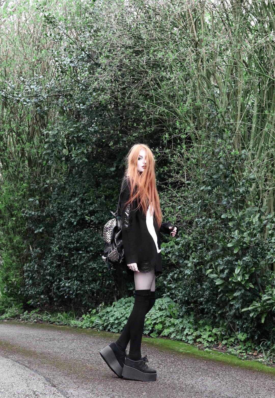 Olivia Emily wears Killstar Luna moon print knit oversized jumper, Asos thigh high socks, Underground triple sole creepers, and Rebecca Minkoff backpack