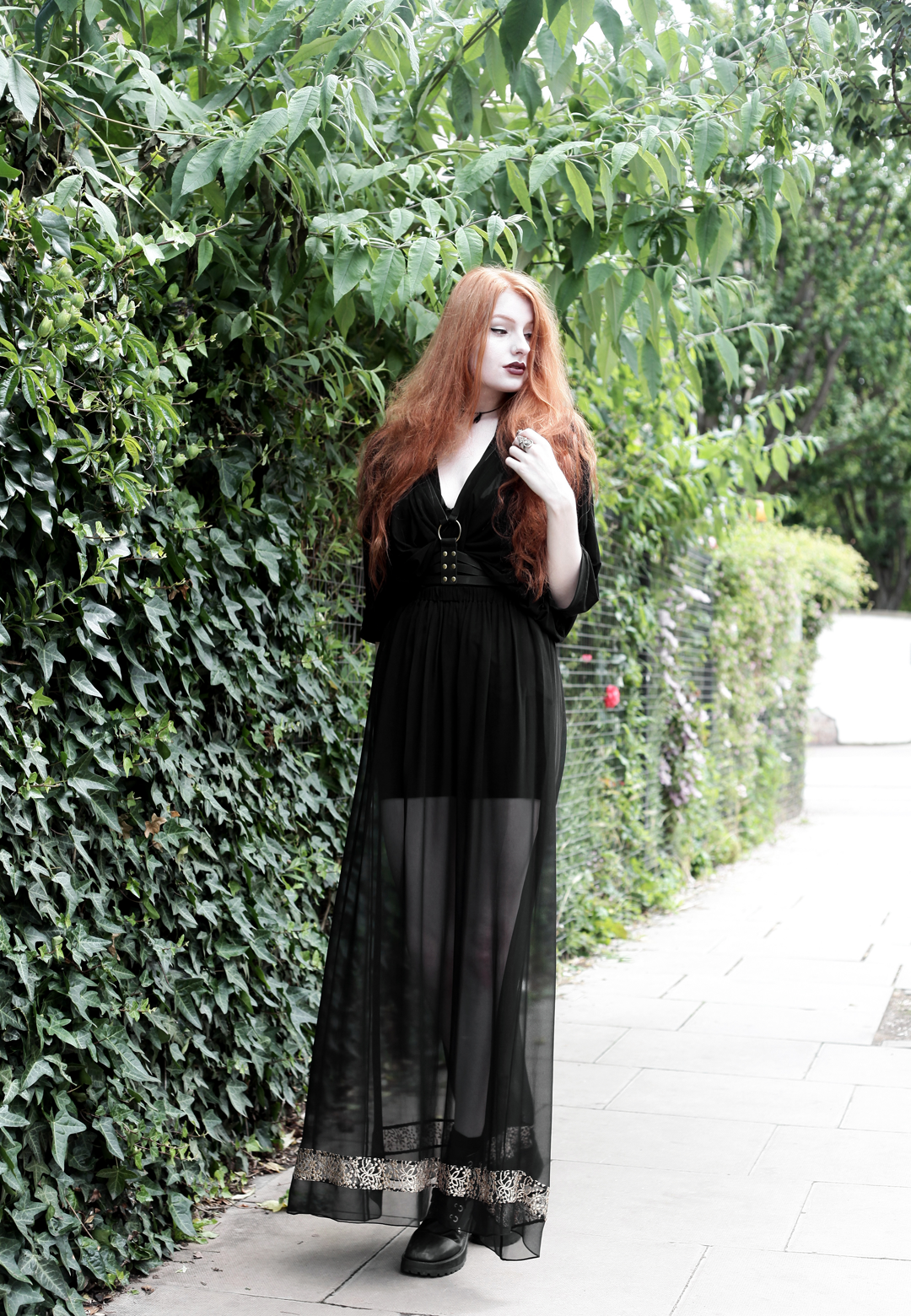Olivia Emily wears Killstar Mesh Top, Dark Thorn Chastity Sheer Maxi Skirt, Asos Harness and Unif Dedi Boots
