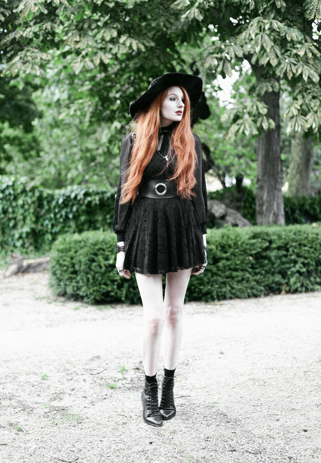 Olivia Emily wears Asos Sheer Shirt, Black Milk Black Lace Skater Dress, Killstar Velvet Witch Brim Hat, Valfre Bowie Choker, Zana Bayne Cincher Waist Belt, and Asos Ariana Lace Up Boots