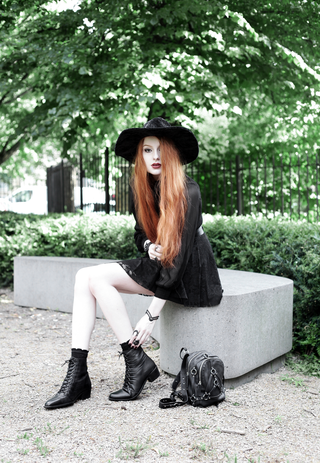 Olivia Emily wears Asos Sheer Shirt, Black Milk Black Lace Skater Dress, Killstar Velvet Witch Brim Hat, Zana Bayne Cincher Waist Belt, Unif Bound Mini Backpack and Asos Ariana Lace Up Boots