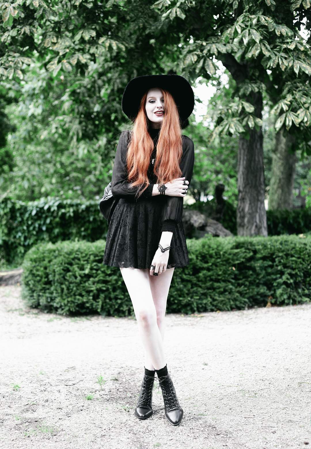 Olivia Emily wears Asos Sheer Shirt, Black Milk Black Lace Skater Dress, Killstar Velvet Witch Brim Hat, Zana Bayne Cincher Waist Belt, and Asos Ariana Lace Up Boots
