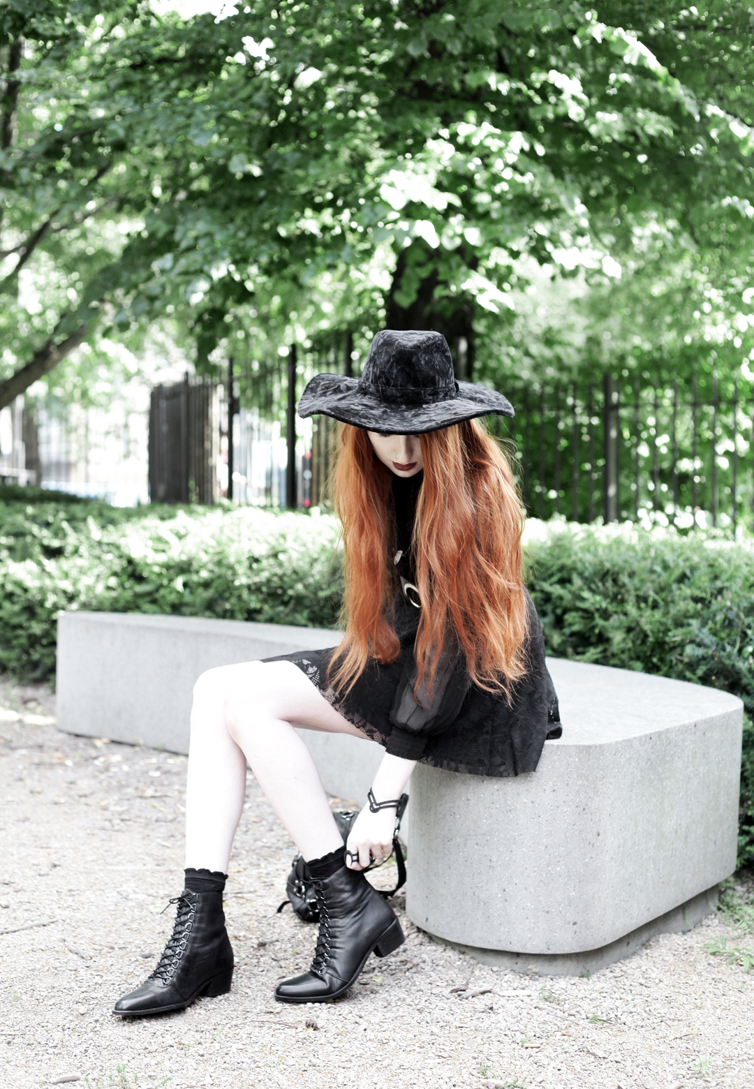 Olivia Emily wears Asos Sheer Shirt, Black Milk Black Lace Skater Dress, Killstar Velvet Witch Brim Hat, Zana Bayne Cincher Waist Belt, Rogue and Wolf Matte Black Bracelet & Rings, and Asos Ariana Lace Up Boots