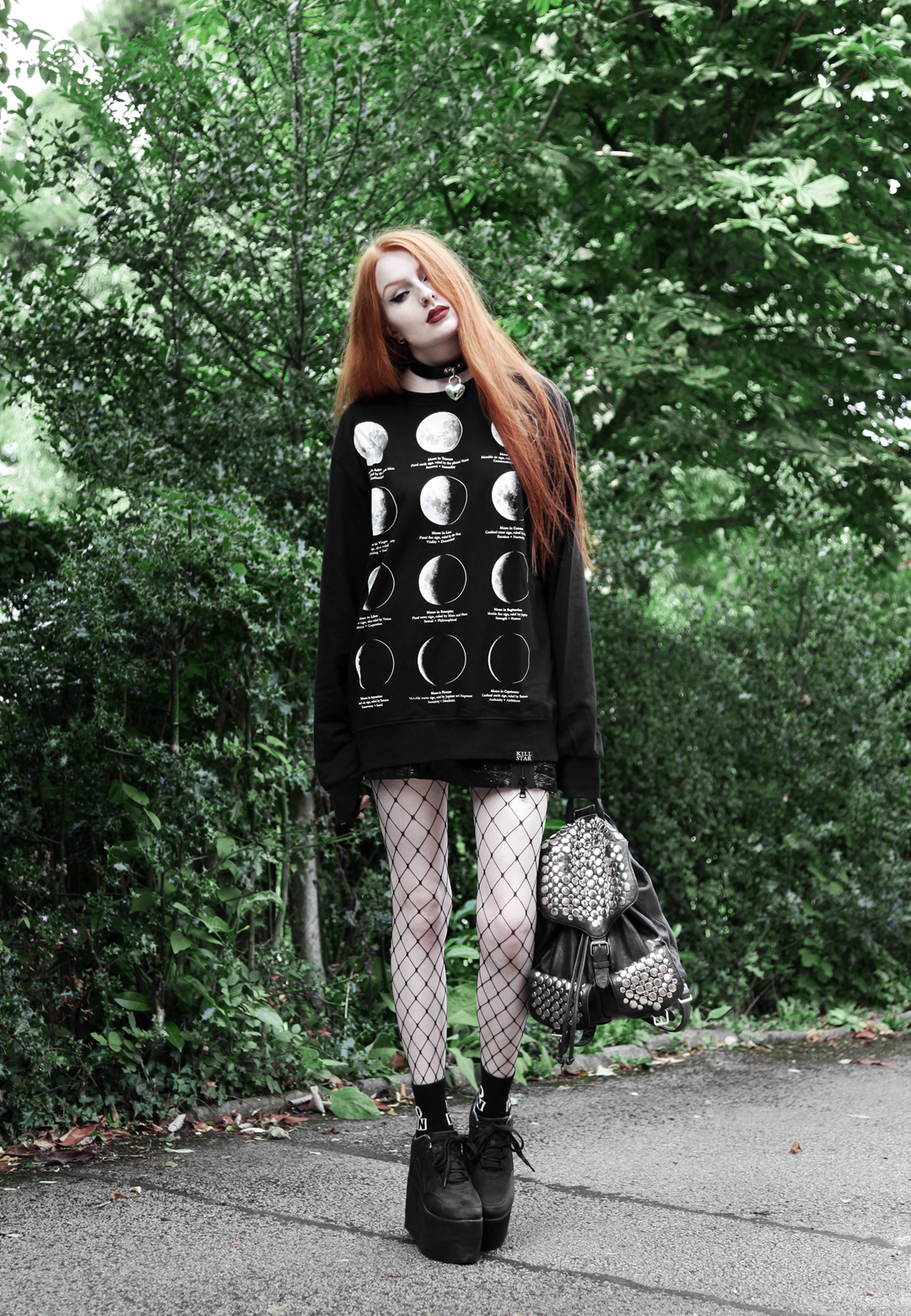 Olivia Emily wears Killstar Emily Heart Locket Choker, Killstar Lunar Moon Phases Sweater, Edun Patent Skirt, Asos Fishnet tights & YRU Qozmo platform shoes