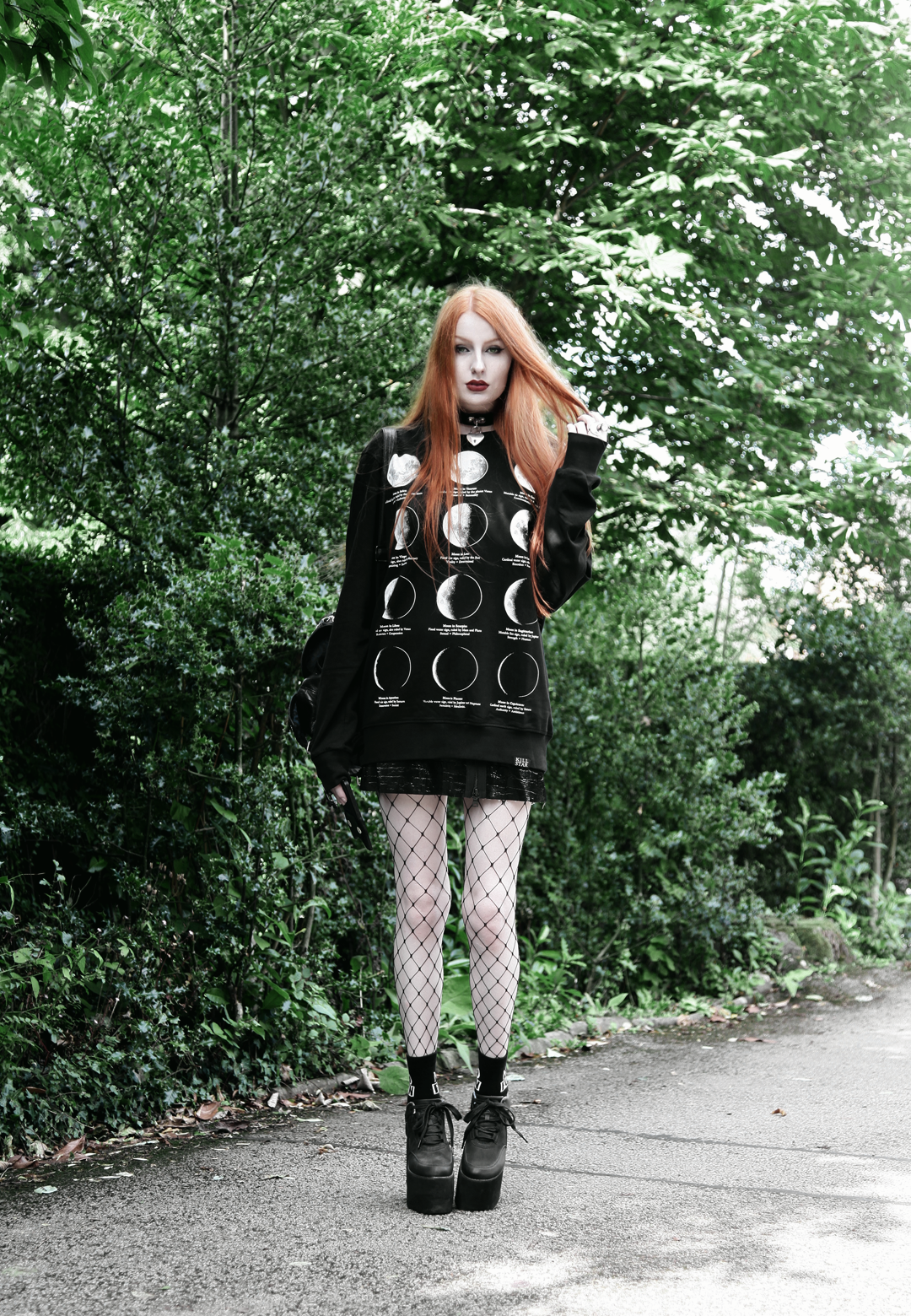 Olivia Emily wears Killstar Emily Heart Locket Choker, Killstar Lunar Sweatshirt, Edun Patent Skirt, Asos Fishnet tights & YRU Qozmo platform shoes