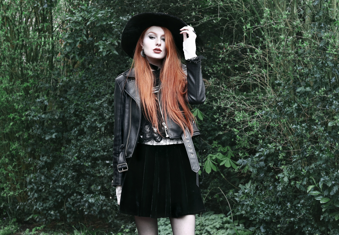 Olivia Emily wears Killstar Lestat shredded knit crop sweater, Killstar Velvet Witch Brim Hat, Unif Biker Jacket, Black Velvet Skirt