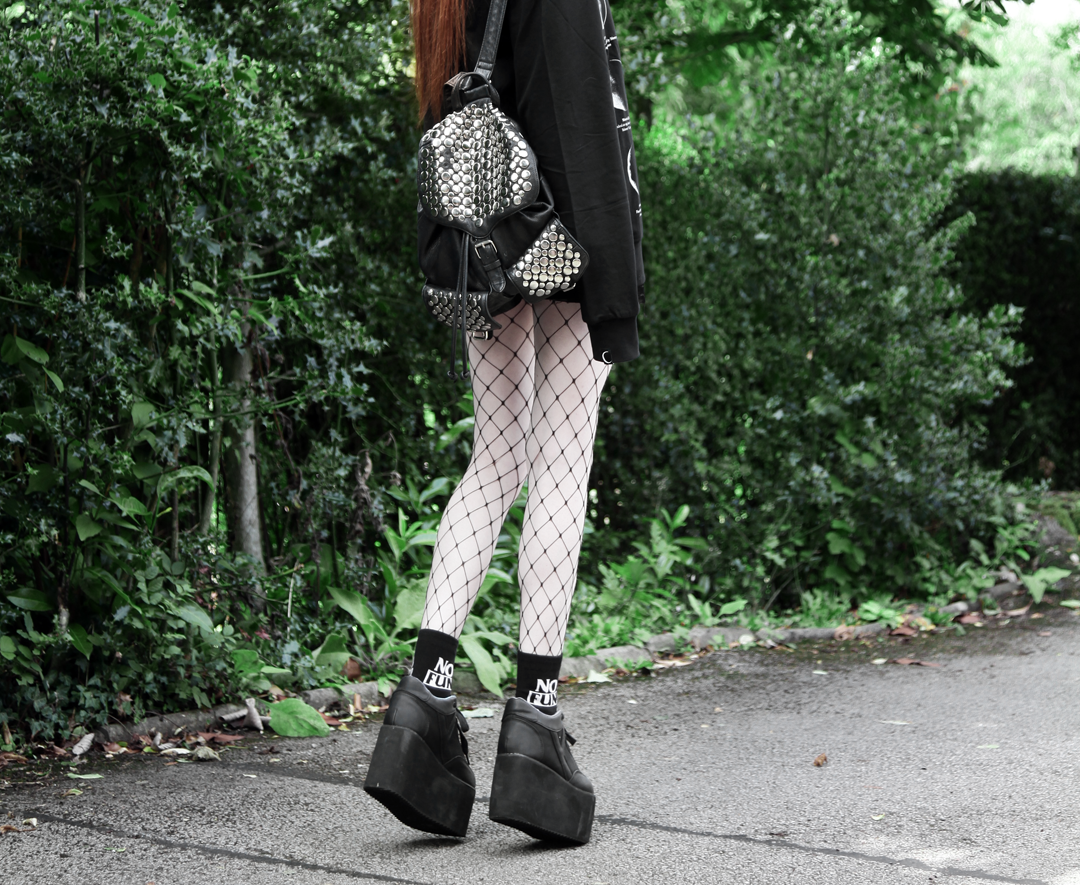 Olivia Emily wears Killstar Lunar Sweatshirt, Edun Patent Skirt, Rebecca Minkoff Studded Backpack, Killstar No Fun Socks, Asos Fishnet tights & YRU Qozmo platform shoes