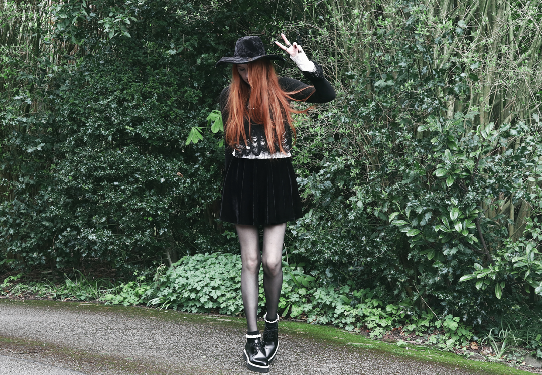 Olivia Emily wears Killstar Lestat shredded knit crop sweater, Killstar Velvet Witch Brim Hat, Black Velvet Skirt, Alexander McQueen platform shoes