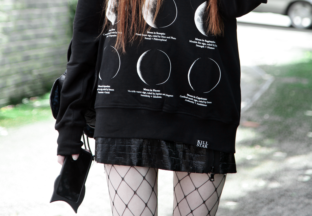 Olivia Emily wears Killstar Emily Heart Locket Choker, Killstar Lunar Moon Phases Sweatshirt, Edun Patent Skirt, Asos Fishnet tights & Valfre Bruno Cat Phone Case