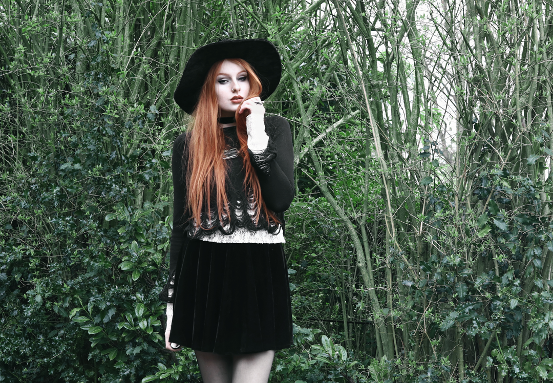 Olivia Emily wears Killstar Lestat shredded knit crop sweater, Killstar Velvet Witch Brim Hat, Black Velvet Skirt