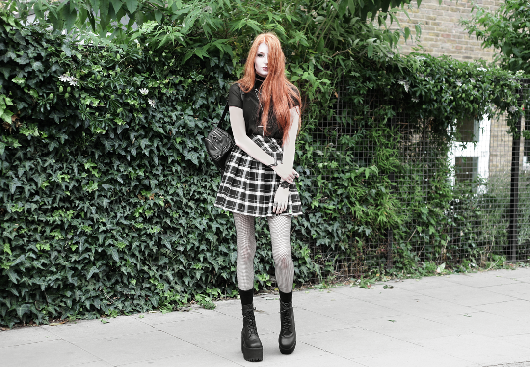 Olivia Emily wears Kiki Minchin Cross Necklace, Killstar sheer shirt, Asos x Le Kilt plaid skirt, Unif Scosche boots