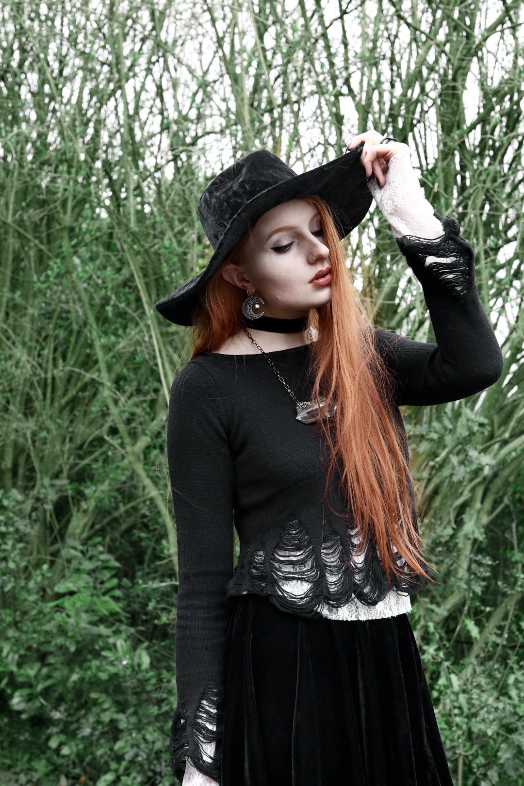 Olivia Emily wears Killstar Lestat shredded knit crop sweater, Killstar Velvet Witch Brim hat, Regalrose Velvet Choker, Serpents Club Quartz necklace, Nyxturna Spike Ring, Rogue And Wolf matte black ring