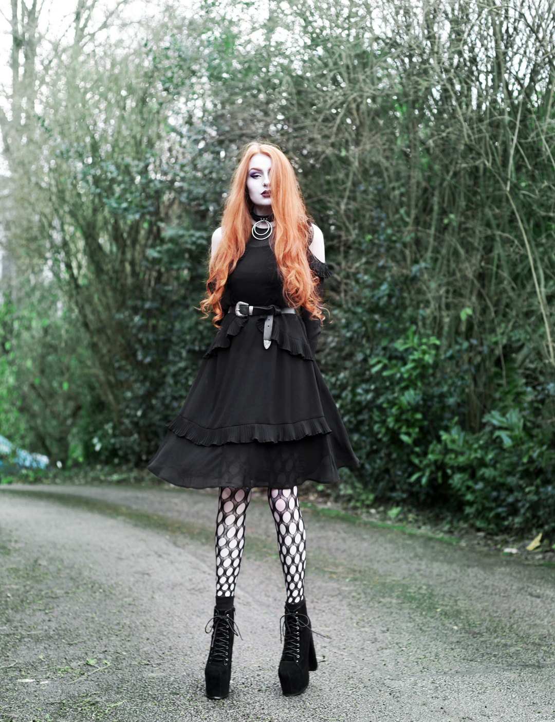 Olivia Emily wears Asos black ruffle midi dress, Killstar Dita Slave collar choker, Asos western belt, Asos pothole tights, and faux suede platform heels boots