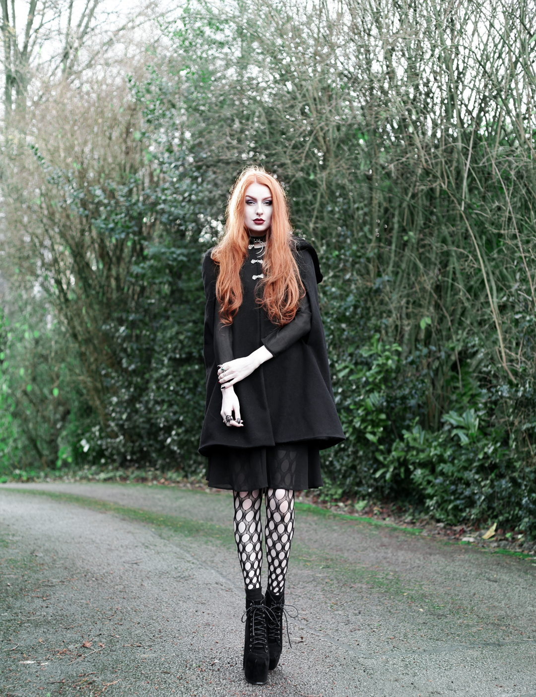 Olivia Emily wears Dark Thorn Clothing Myrtle Cape, Asos black ruffle midi dress, Killstar Dita Slave collar choker, Asos western belt, Asos pothole tights, faux suede platform heels boots