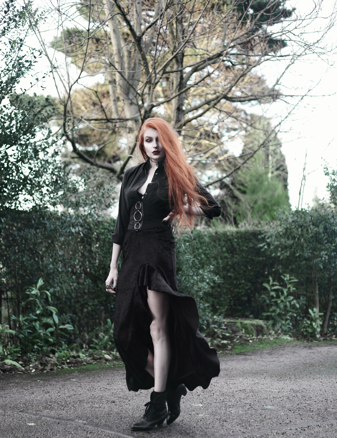 Olivia Emily wears Black Shirt, Asos Triple Ring Belt, Rokoko Velvet Ruffle High Low Maxi Skirt, and Vintage Pointed Boots