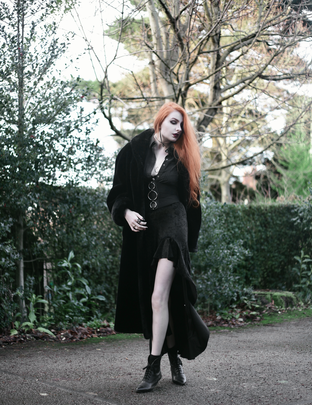 Olivia Emily wears a Maxi Fax Fur Coat Black Shirt, Asos Triple Ring Belt, Rokoko Velvet High Low Ruffle Skirt, and Vintage Pointed Boots