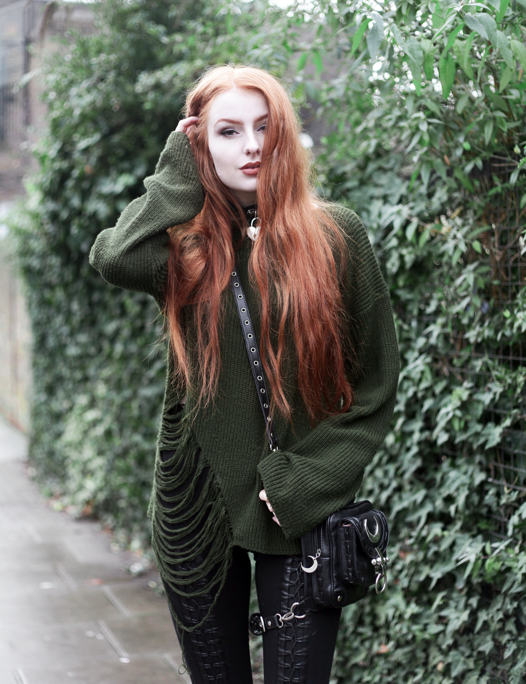Olivia Emily wears Asos Bones Oversized jumper, Restyle pl harness bag, Stylestalker lace up leggings trousers, and Killstar Emily Padlock choker collar