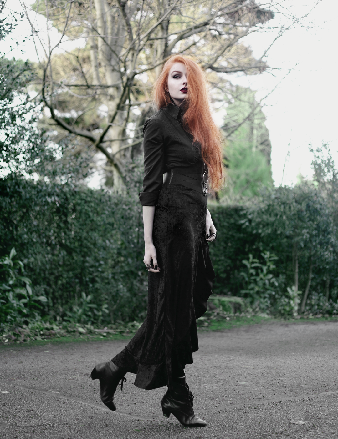 Olivia Emily wears Black Shirt, Asos Triple Ring Belt, Rokoko Velvet High Low Ruffle Skirt, and Vintage Pointed Boots