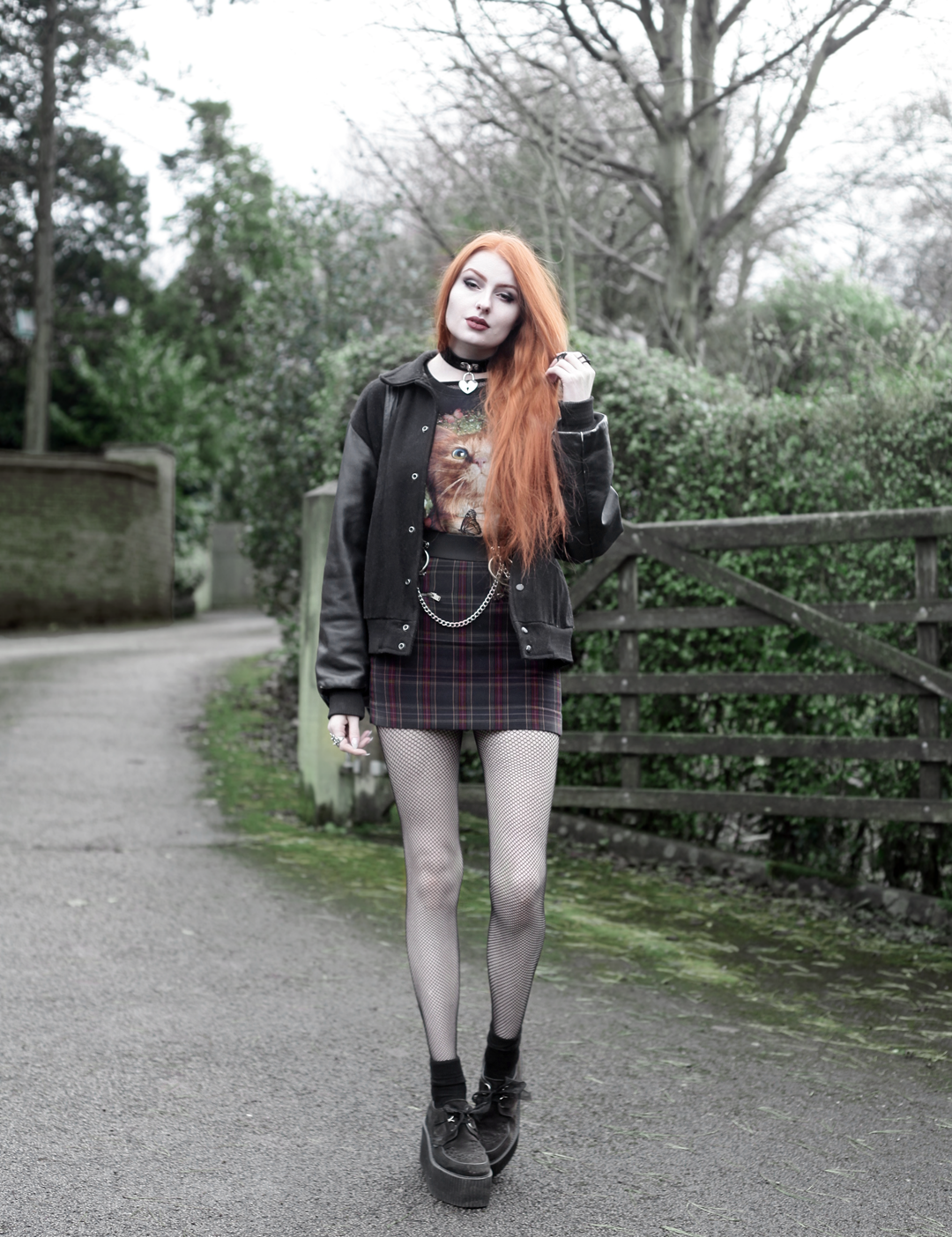 Olivia Emily wears Vintage Cat Tee, fishnet long sleeve top, Mary Wyatt Belt, Plaid Skirt, and Underground Creepers