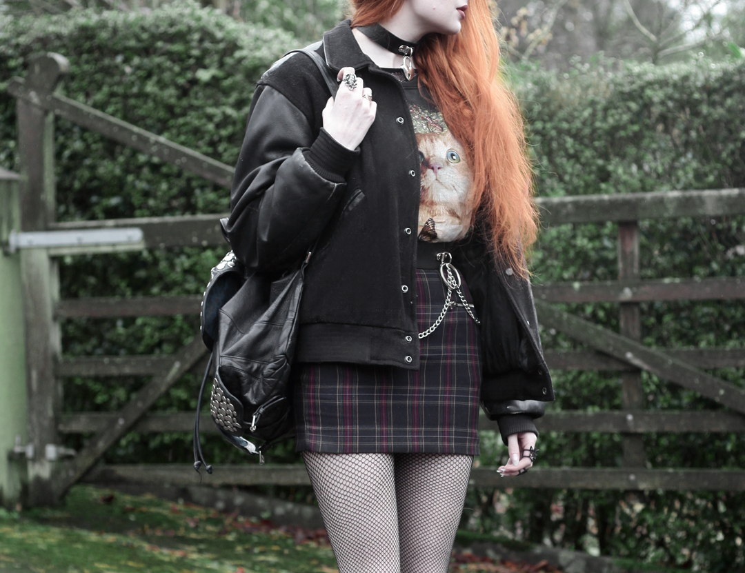 Olivia Emily wears Vintage Cat Tee, fishnet long sleeve top, Mary Wyatt Belt, Plaid Skirt, and Rebecca Minkoff Backpack