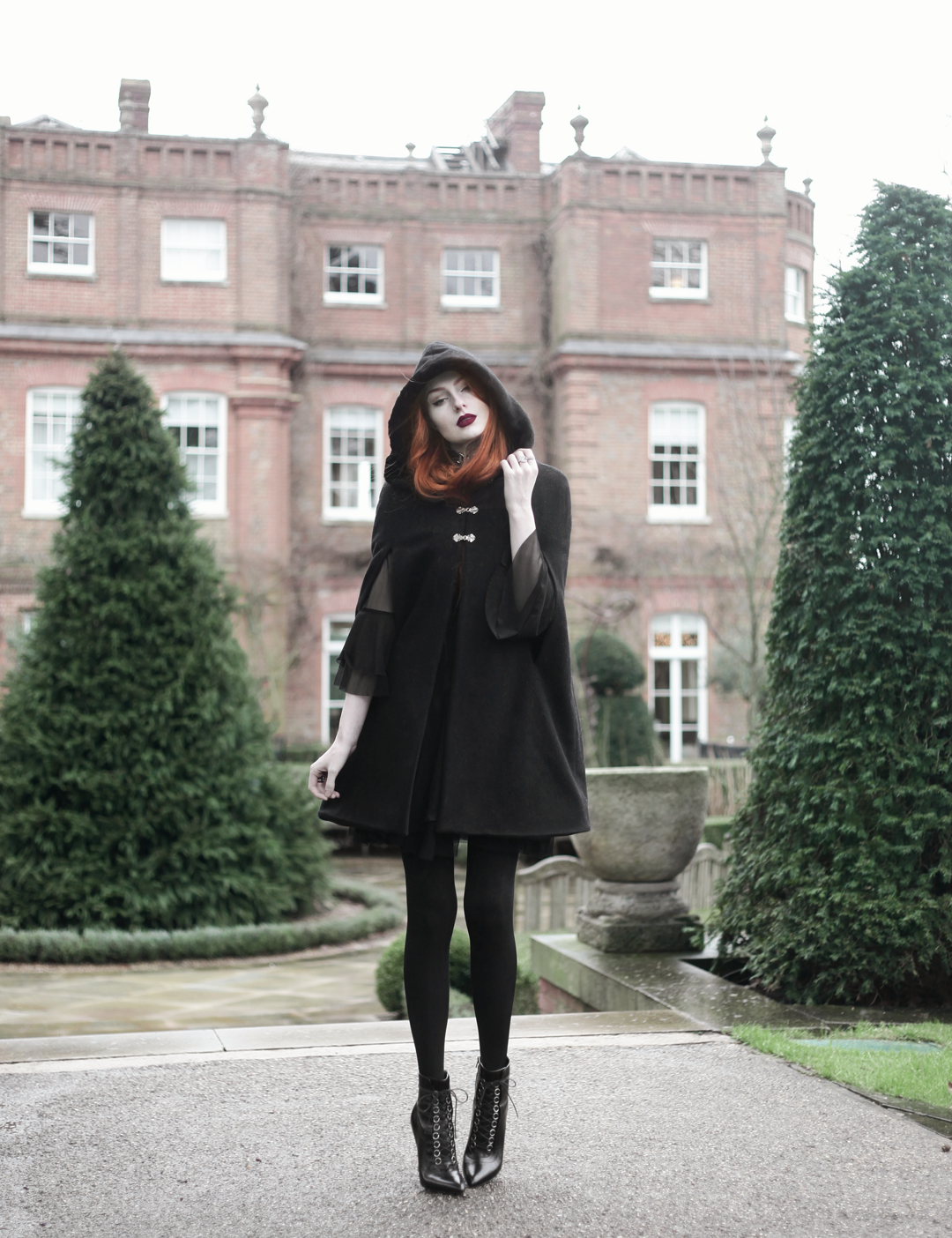 Olivia Emily wears Dark Thorn Clothing Cape, Killstar Nu Decay Dress, and Saint Laurent Fetish Ankle Boots