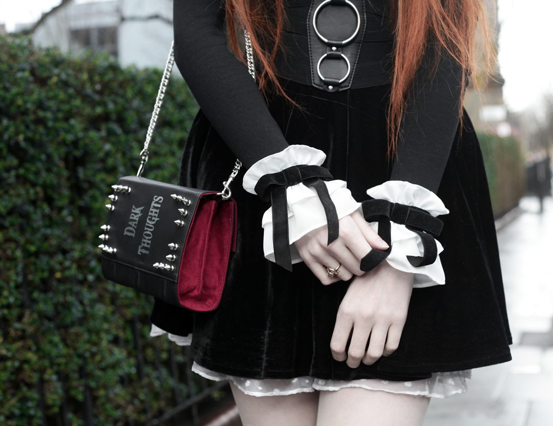 Olivia Emily wears Skinny Bags Dark Thoughts Clutch, River Island High Neck Top, Asos Ruffle Cuffs, and Black Velvet Skirt