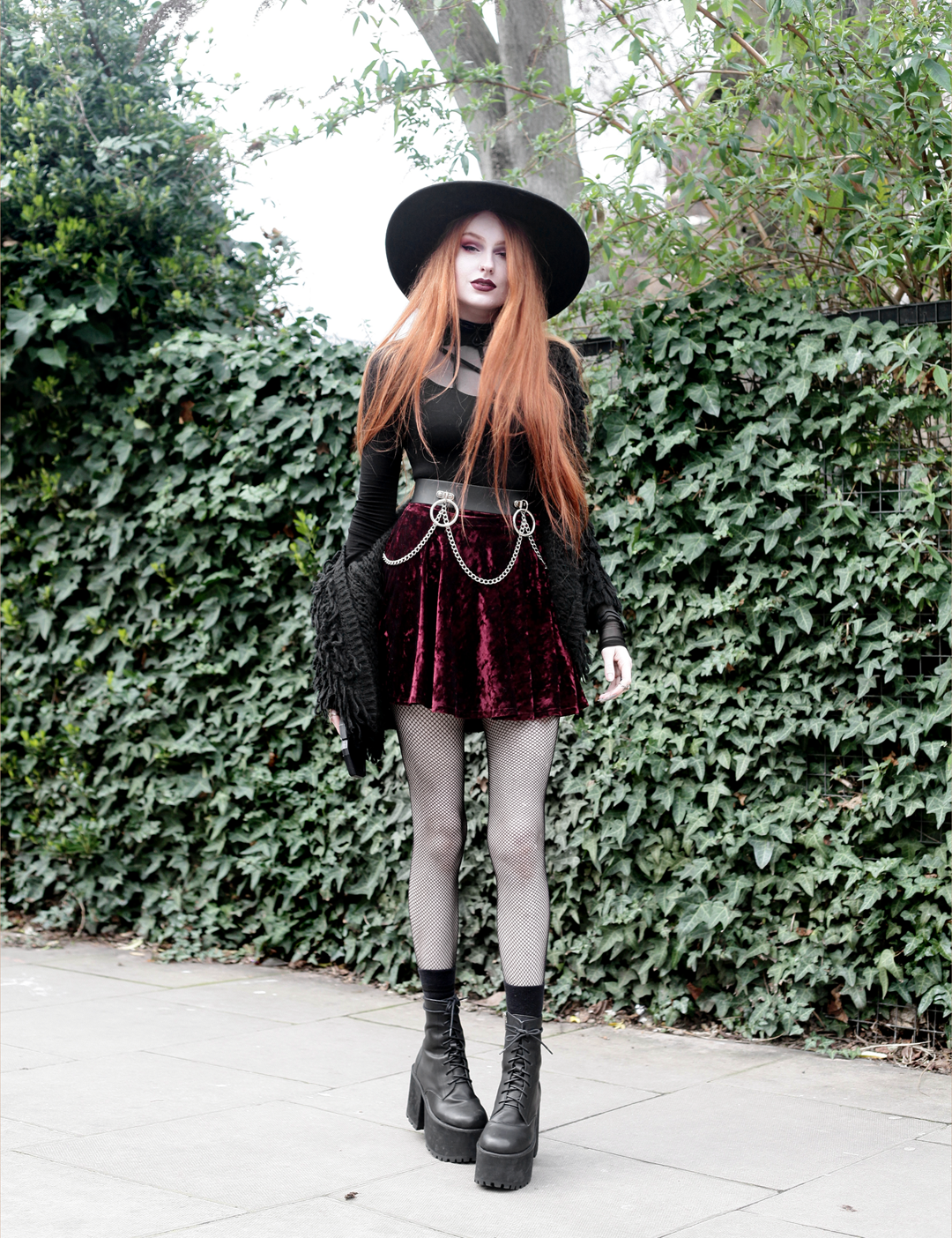 Olivia Emily wears Rogue and Wolf Moondoll Top, Killstar Fedora Hat, Crushed Velvet skirt, Mary Wyatt Chain Belt and Unif Scosche Boots