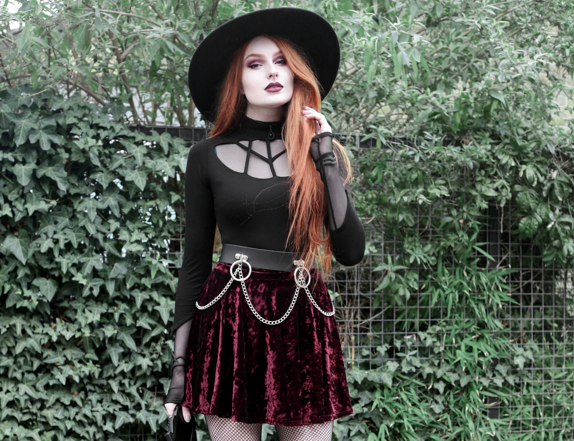 Olivia Emily wears Rogue and Wolf Moondoll Top, Killstar Fedora Hat, Crushed Velvet skirt, and Mary Wyatt Chain Belt