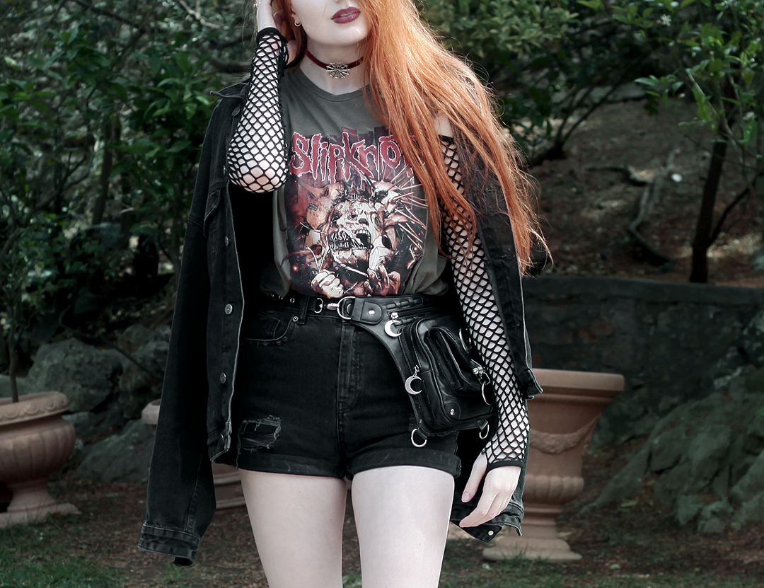 Olivia Emily Wears Slipknot Tank Band Tee, Asos Fishnet Sleeve Bodysuit, Black Denim Shorts, and Regalrose Spiderweb choker