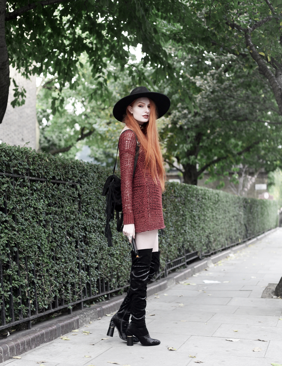 Olivia Emily wears Unif Knit Jumper, Asos Fringe Backpack, Killstar Witch Brim Hat, and Ego Velvet Over Knee Boots