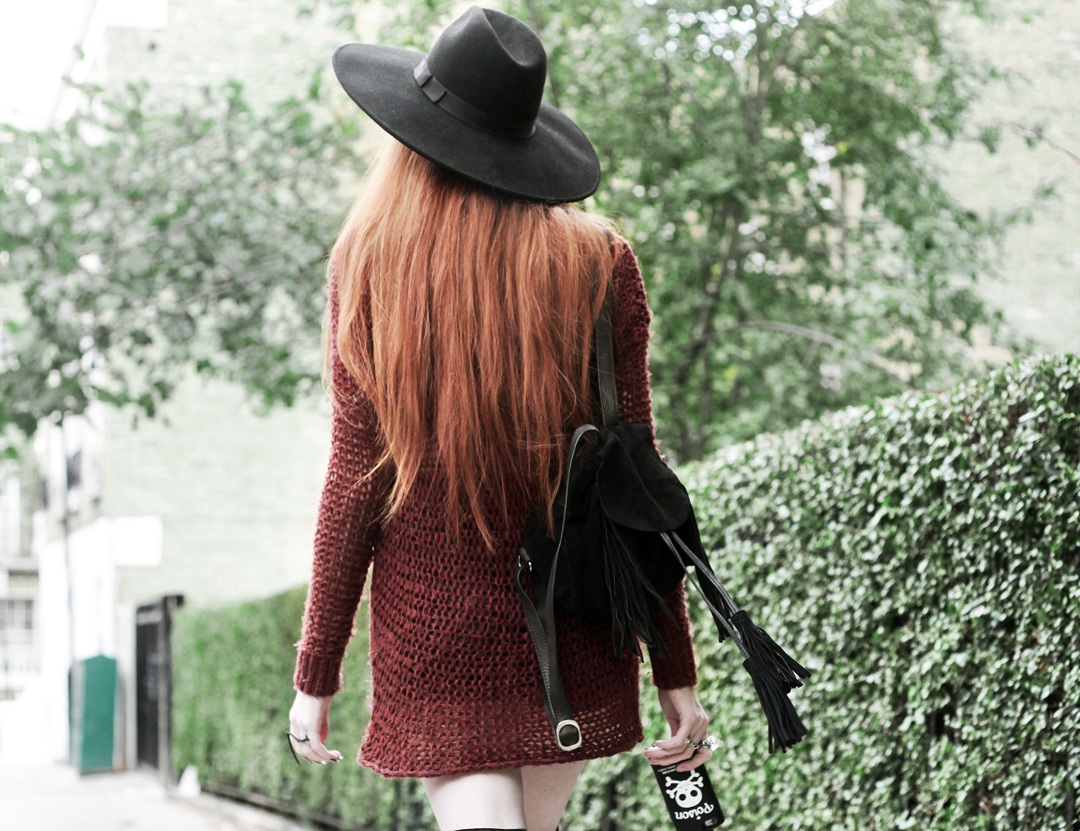 Olivia Emily wears Unif Knit Jumper, Asos Fringe Backpack, Killstar Witch Brim Hat, and Valfre Poison Bottle Phone Case