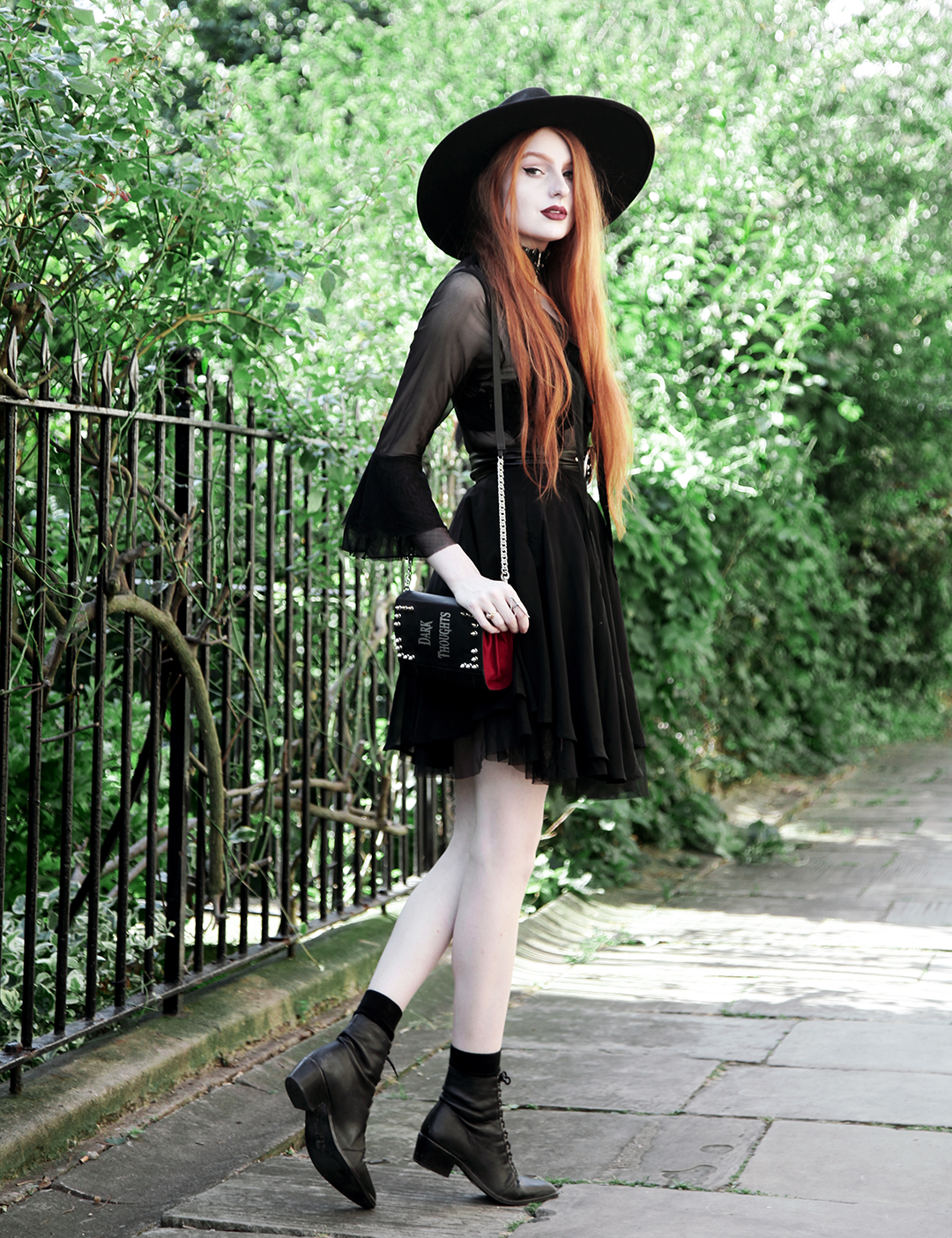 Olivia Emily wears Killstar Witch Brim Hat, Killstar Decay Nu-Mourning dress, Pheren Couture Sword Choker, Skinnybags Dark Thoughts Book Clutch and Asos Pointed Toe Boots
