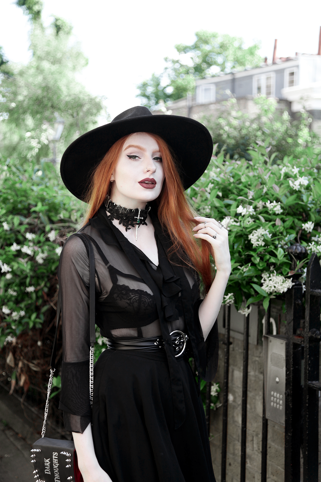 Olivia Emily wears Killstar Witch Brim Hat, Killstar Decay Nu-Mourning dress, Pheren Couture Sword Choker, Asos Eyelet Waist Belt and Skinnybags Dark Thoughts Book Clutch